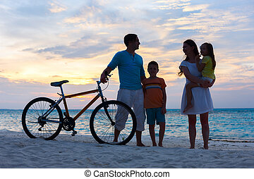 Family with a bike at tropical beach - Silhouettes of a...