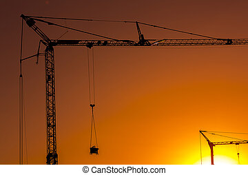 Building site with cranes in sunset silhouette scaffolding...