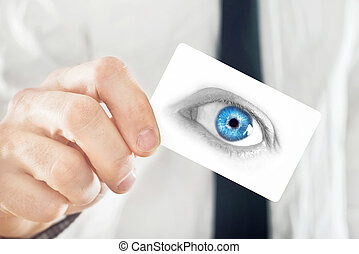 Opthalmologist giving his visiting card, selective focus on...