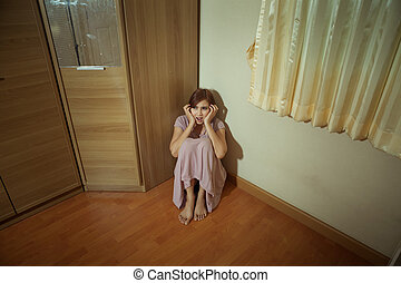 Scared abused woman sitting in the corner of the room
