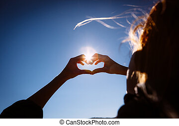 Hands making love shape sign on bright blue sky. - Hands...