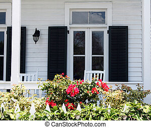 White front porch with black shutters and rockers.