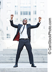 The best day ever! Full length of happy young African man in...