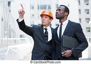 Discussing building project. Confident contractor in hardhat pointing away while standing together with African businessman