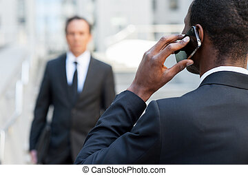 Business world. Rear view of African man in formalwear talking on the mobile phone while another businessman walking on background