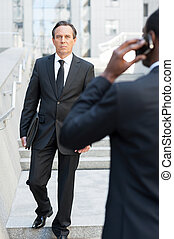 Business people. Rear view of African man in formalwear talking on the mobile phone while another businessman walking by stairs on background