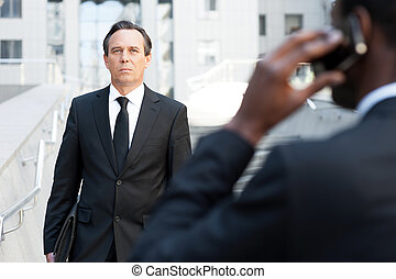Confident business expert. Rear view of African man in formalwear talking on the mobile phone while another businessman walking by stairs on background