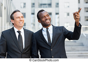 Showing the opportunities. Two cheerful business men talking and gesturing while standing outdoors