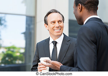 Having a coffee break to talk around. Two cheerful business men talking and gesturing while standing outdoors