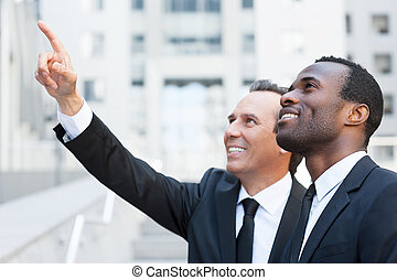Look over there! Side view of two cheerful business men talking and gesturing while standing outdoors