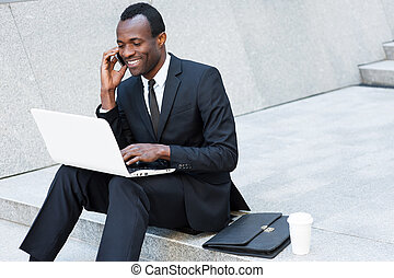 Business is his life Cheerful young African man in...