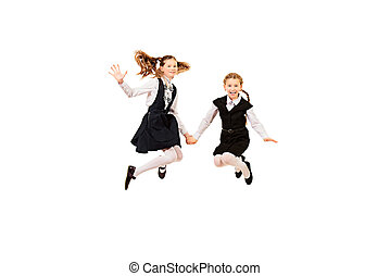 girls jumping - Two ten years girls in a uniform jumping for...