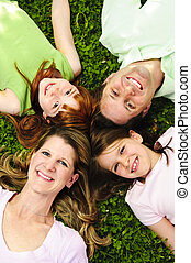 Happy family - Portrait of happy family laying on grass...
