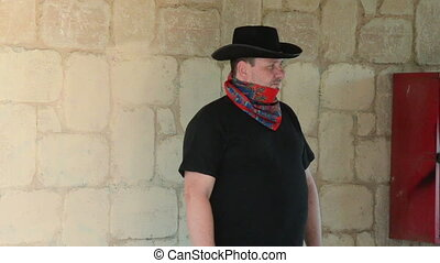 Cowboy wearing bandana scarf - Cowboy in black hat wearing...