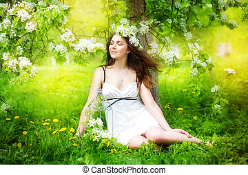 Portrait of a beautiful young woman in a wreath of spring...