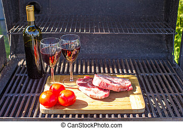 Fresh meat, vegetables and bottle of wine on a picnic outdoors