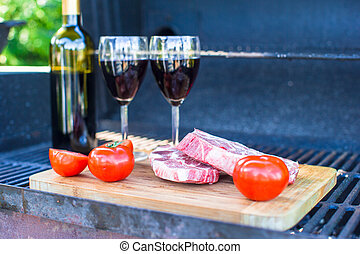 Fresh meat, vegetables and bottle of wine on barbecue outdoors