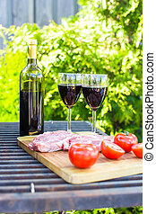 Juicy steak, vegetables and bottle of wine on a picnic outdoors