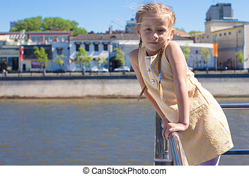 Little adorable girl on the deck of a ship sailing in big...
