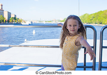 Little adorable girl relaxing on a luxury ship sailing in...