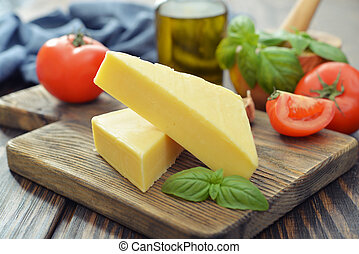 Hard cheese with basil on wooden cutting board