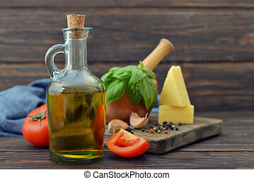 Olive oil in bottles with tomato, garlic and basil on wooden...