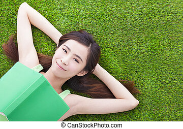 young woman laying down  on a meadow with books