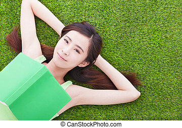 smiling girl student  laying down  on a meadow with books