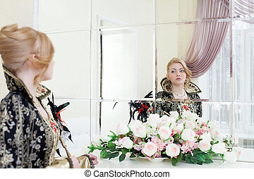 Young actress looking at her reflection in mirror - Portrait...