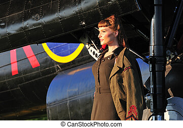 pretty lady in army uniform with WWII bomber - retro...