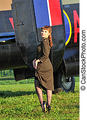 Army pinup girl with WWII bomber - sexy woman in an army...