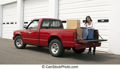 Attractive Female Loads Red Pickup Truck Storage Facility...