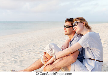 couple at vacation - young couple sitting at the beach,...