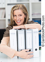 Happy confident businesswoman hugging files - Happy...