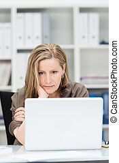 Businesswoman staring glumly at her laptop computer as she...