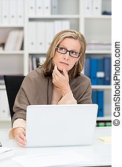 Pensive middle-aged businesswoman wearing glasses sitting at...