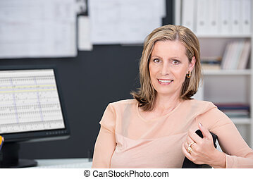 Middle-aged businesswoman sitting at her desk