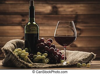 Bottle of red wine, glass and grape on a sack in wooden...