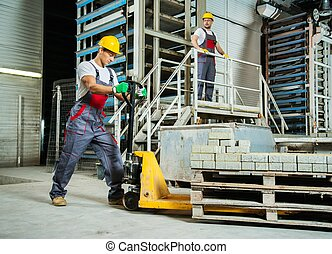 Young worker moving paving stones with pallet truck on a...