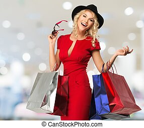 Smiling young blond woman with shopping bags in shop...