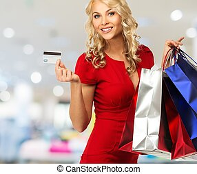 Smiling young blond woman with shopping bags and payment...