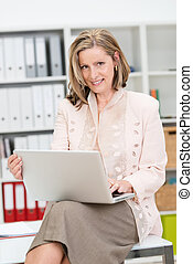 Businesswoman balancing her laptop on her knee as she sits...