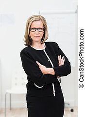 Confident austere middle-aged businesswoman wearing glasses...
