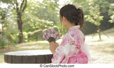 Asian woman in kimono waving a fan