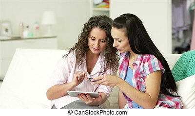 Online Shopping with Friend - Two girlfriends inputting card...