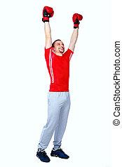 Full length portrait of a happy boxer man winner raising...