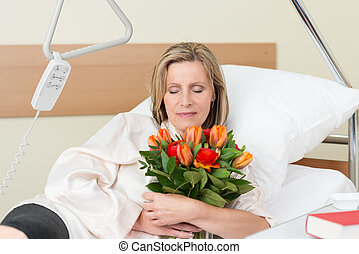 Sad woman clutching a bunch of roses in hospital