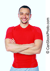 Cheerful sports man standing with arms folded over white...