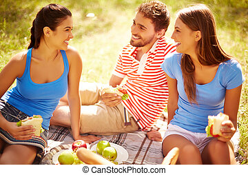 Having snack - Happy young friends having picnic in the...