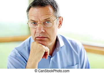 Senior man in glasses looking at camera